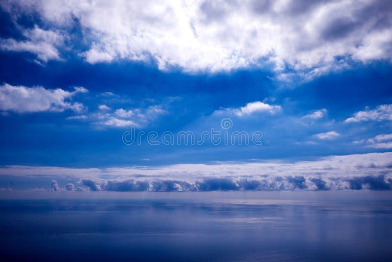 Blauer Himmel, weiße Wolken und ruhiges blaues Meer stockfotografie