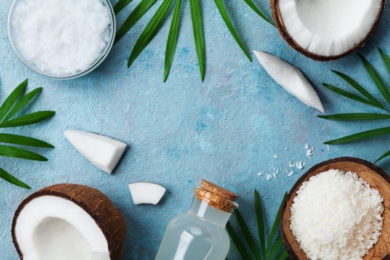 Blauer Hintergrund mit Satz organischen Kokosnussprodukten für Badekur, Kosmetik oder Lebensmittelinhaltsstoffe Öl, Wasser und Sc lizenzfreie stockfotos