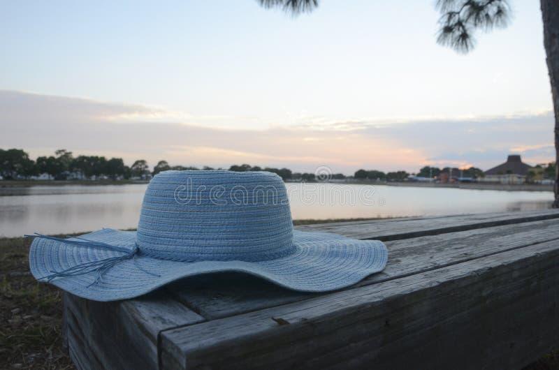 Blauer Hut auf Bank bei Sonnenuntergang stockbild