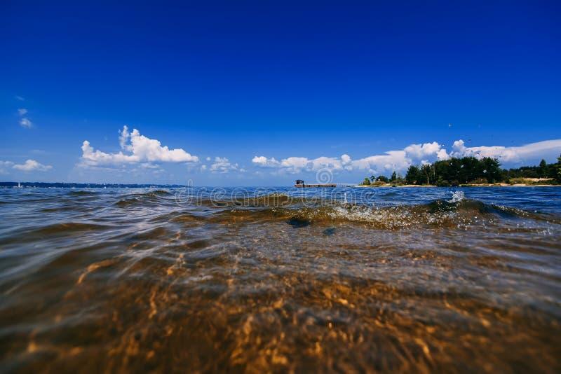 Blauer klarer Himmel mit weißen Wolken über Wasser am Sommertag und Strand mit Wellen lizenzfreie stockbilder