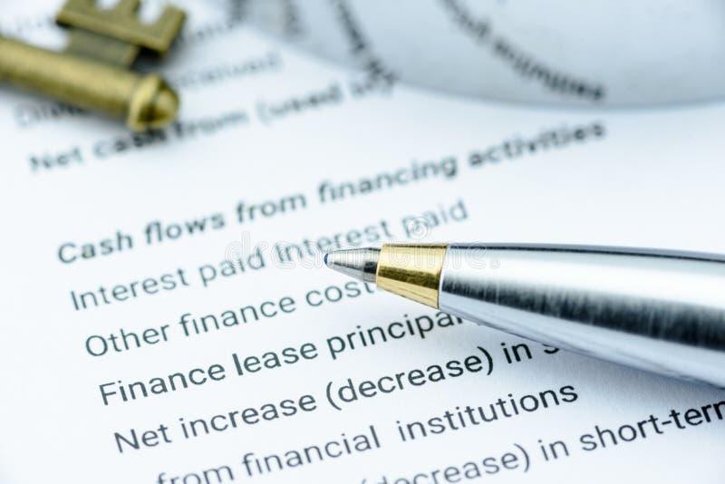 Blauer Kugelschreiber auf dem Jahresbericht eines Unternehmens, wenn die Aussage über Bargeldumläufe vom einzelnen Analytiker ana lizenzfreie stockfotos