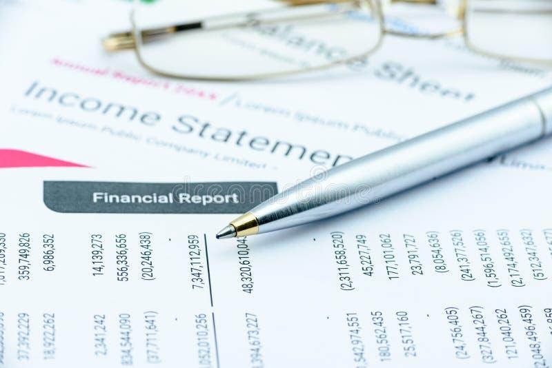 Blauer Kugelschreiber auf einem vierteljährlichen Unternehmensfinanzbericht über eine Tabelle lizenzfreie stockfotos