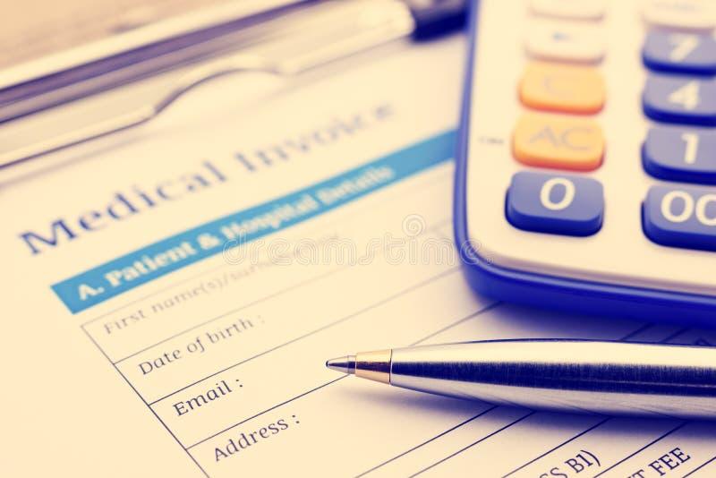 Blauer Kugelschreiber, ein Taschenrechner und eine medizinische Rechnung auf einem Klemmbrett stockbilder