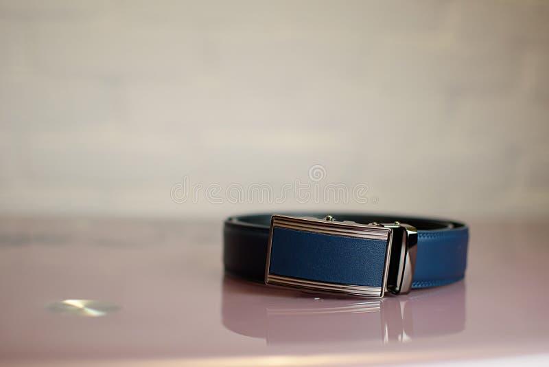 Blauer lederner Manngurt auf einer Tabelle stockfoto