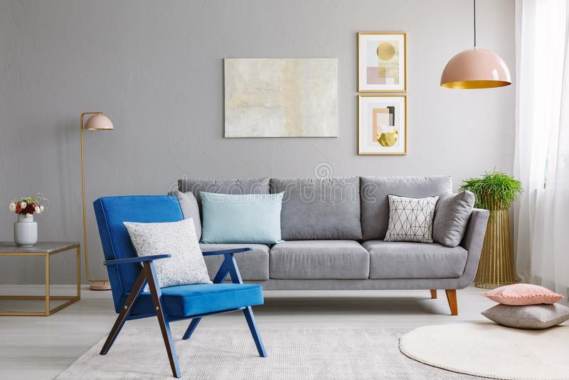 Blauer Lehnsessel nahe grauem Sofa in modernes Wohnzimmer Innenwi lizenzfreie stockbilder