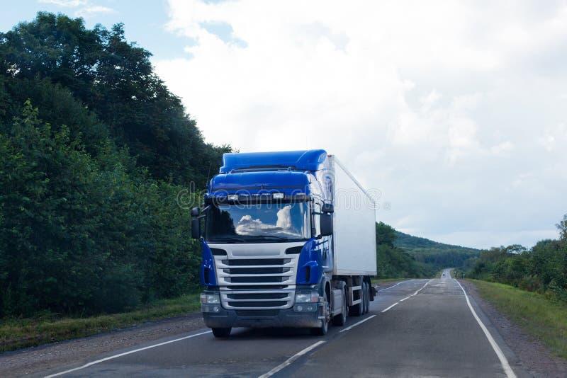 Blauer LKW auf einer Straße lizenzfreie stockfotografie
