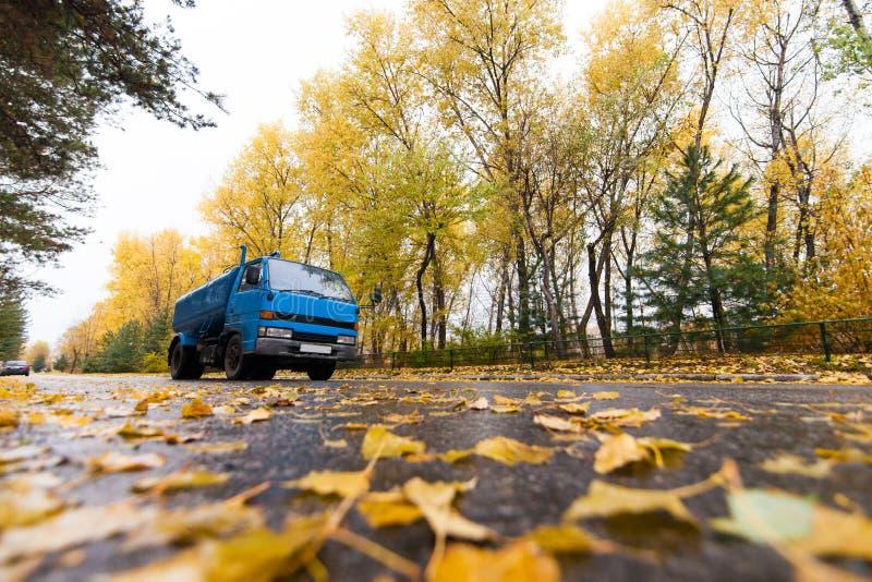 Blauer LKW auf Herbststraße stockbild