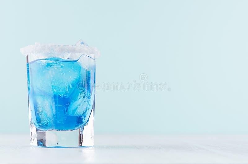 Blauer Margarita Getränk des kühlen Sommers für Partei mit Eiswürfeln, Salzkante auf weißem hölzernem Brett und tadellose Farbwan stockfoto