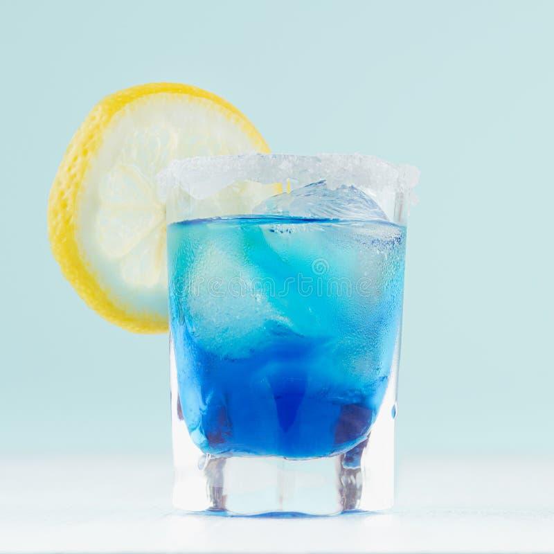 Blauer Margarita Getränk des kühlen Sommers für Partei mit Eiswürfeln, Salzkante, Zitronenscheibe auf weißem hölzernem Brett und  lizenzfreies stockfoto