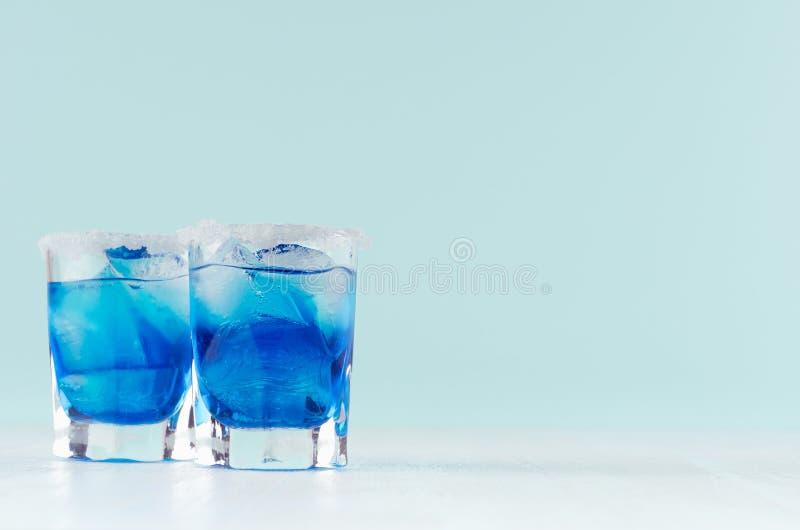 Blauer Margarita Getränk des kühlen Sommers für Partei mit Eiswürfeln, Salzkante in zwei nass Schnapsgläsern auf weißem hölzernem stockbilder