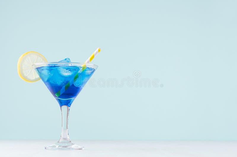 Blauer Margarita Getränk des kühlen Sommers für Partei mit Eiswürfeln, Zitronenscheibe, gelbem Stroh auf weißem hölzernem Brett u stockfoto