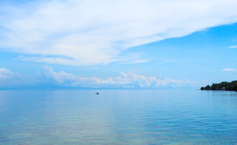 Blauer Meerblick mit Fischerboot und blauer Himmel Entspannende Seeansicht mit ruhigem Meerwasser lizenzfreie stockfotos