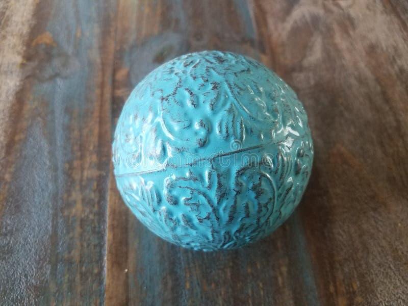 Blauer Metallball auf braunem Holztisch stockfoto
