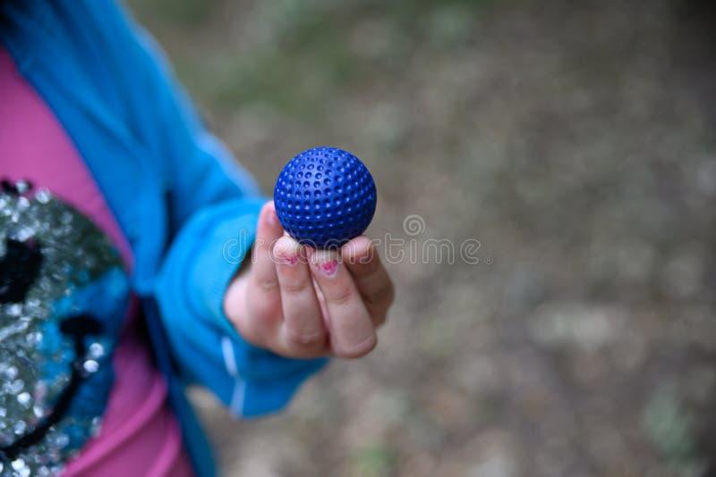 Blauer Minigolfball in der Hand eines jungen Mädchens lizenzfreie stockbilder