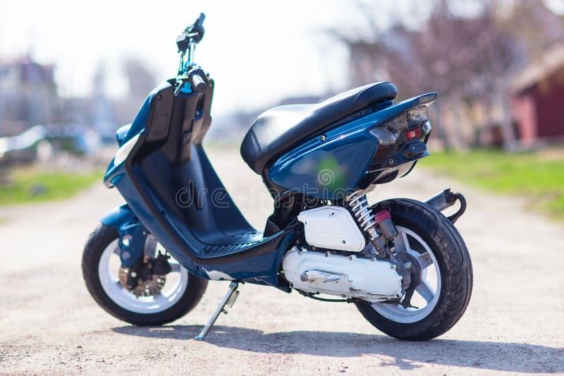 Blauer moderner Roller auf der Schotterstraße stockfotografie
