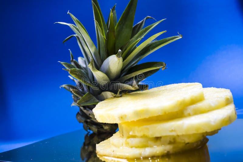 Blauer monophonischer Hintergrund Die frische geschnittene Ananas auf runden Segmenten Grün Blätter Tropische Frucht Vitamine und lizenzfreie stockbilder