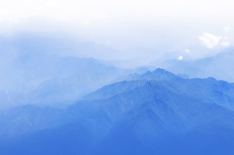 Blauer nebelhafter Berg stockfotografie