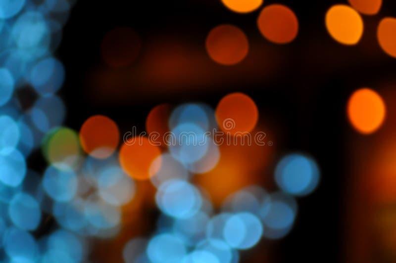 Blauer, orange, roter und dunkler abstrakter heller Hintergrund, buntes bokeh, glänzende Lichter des Kreises, funkelndes funkelnd lizenzfreie stockfotos
