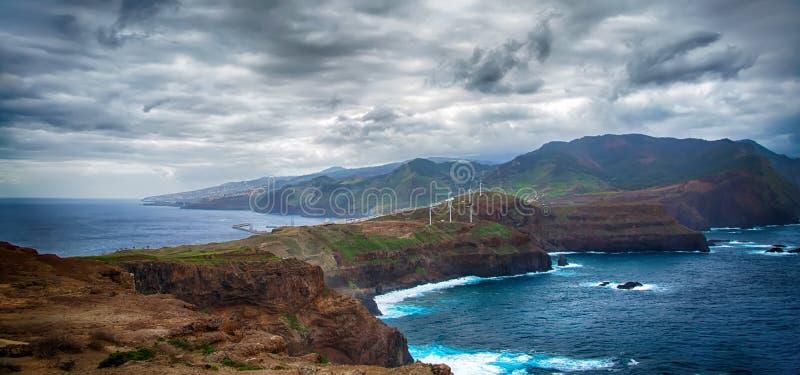 Blauer Ozean, Berge, Felsen, Windmühlen und bewölkter Himmel stockfotos