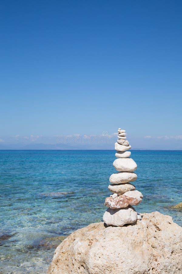 Blauer Ozeanhintergrund mit einer Säule von Steinen für nachdenkliches oder lizenzfreies stockbild