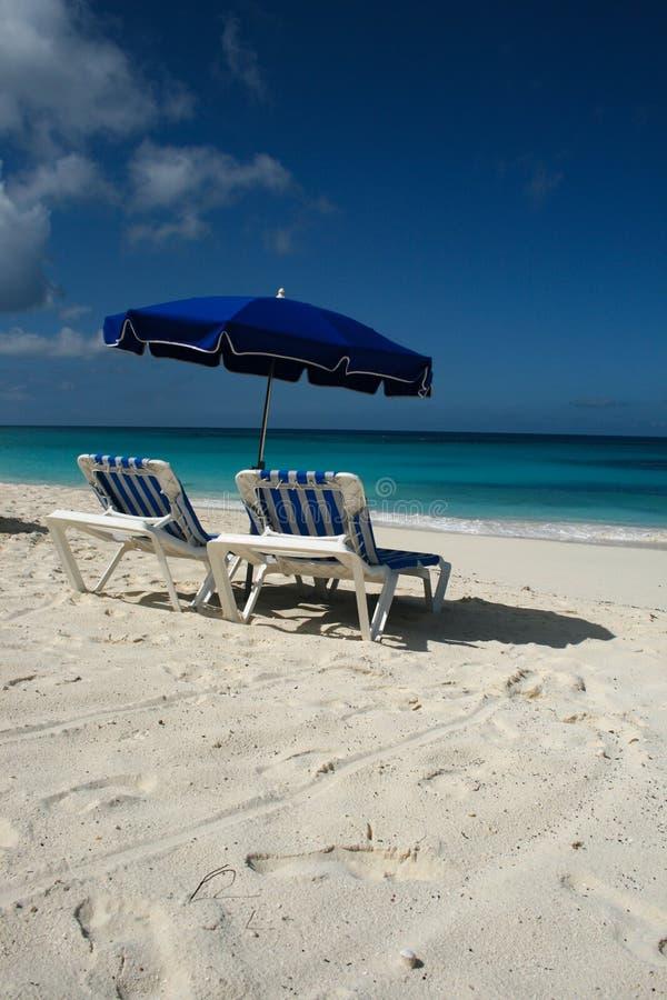 Blauer Regenschirm und Stühle auf karibischer Anguilla setzen auf den Strand lizenzfreie stockbilder
