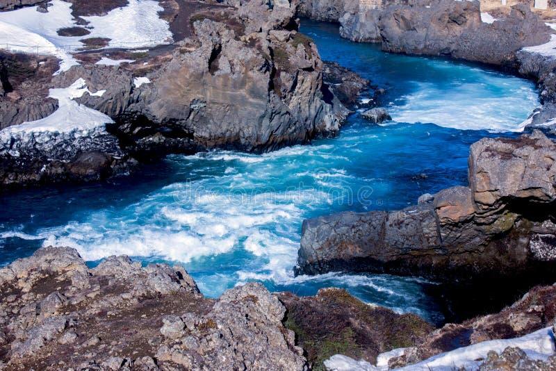 Blauer, rei?ender Fluss umgeben durch Lavafelsen stockbild