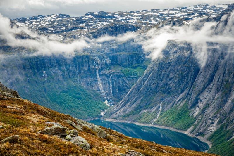 Blauer See umgeben durch die steilen Klippen, die in den Wolken, Odda, Hordaland-Grafschaft, Norwegen sich verstecken lizenzfreie stockbilder