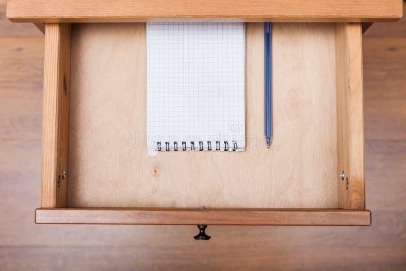 Blauer Stift und quadratisches Notizbuch im offenen Fach stockbild