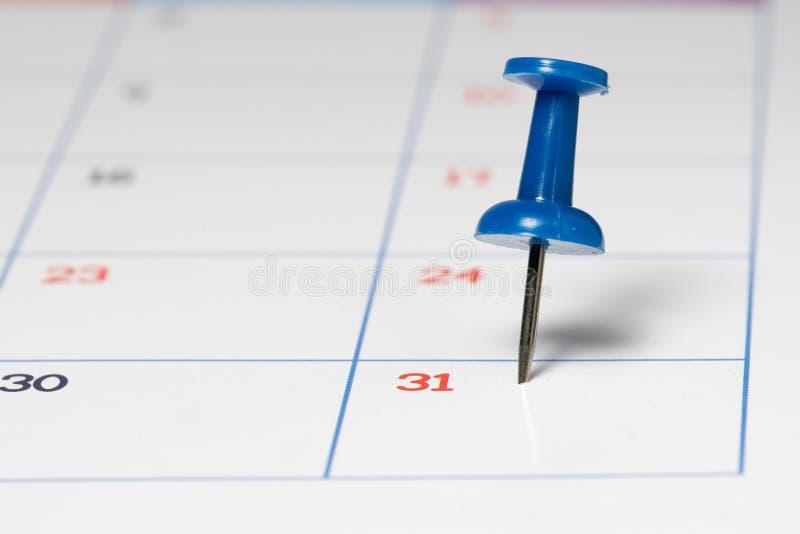 Blauer Stoß Pin auf Kalender stockfotografie