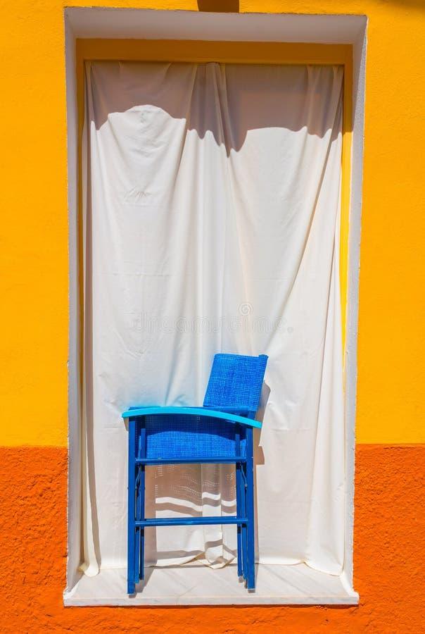 Blauer Stuhl im Fenster stockbild