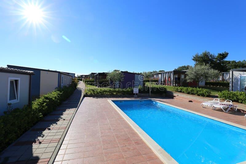 Blauer Swimmingpool durch die neuen Wohnmobile stockfotografie