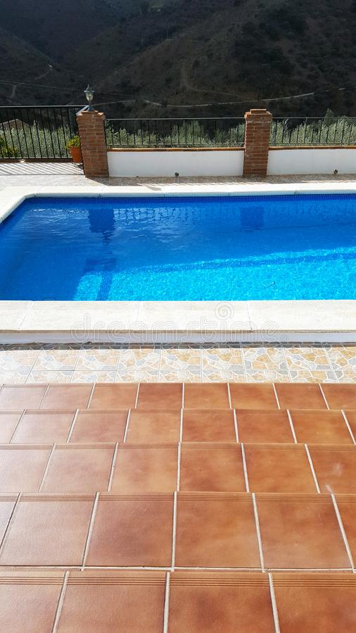 Blauer Swimmingpool mit braunen Fliesen, Geländern und Bäumen hinten stockfoto