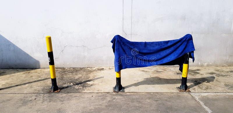 Blauer Täter, Baumwolle, Teppich oder Stoff, der auf einem kleinen, gelben/schwarzen Turm hängt stockfotos