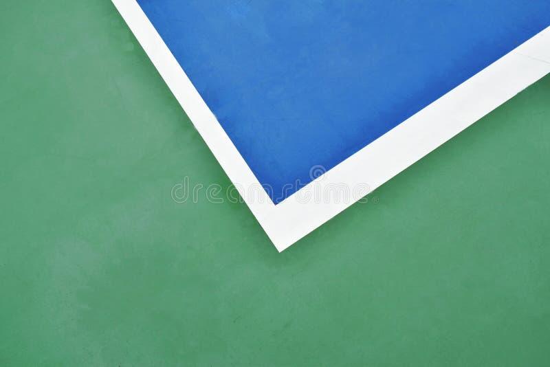 Blauer Tennisplatz mit weißer Grenze auf grünem Boden stockbild