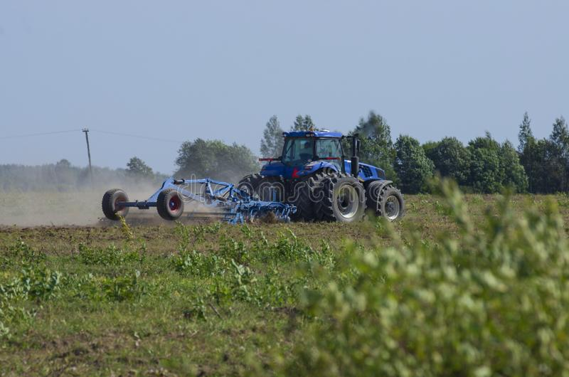 Blauer Traktor, der das grüne Feld pflügt stockfoto