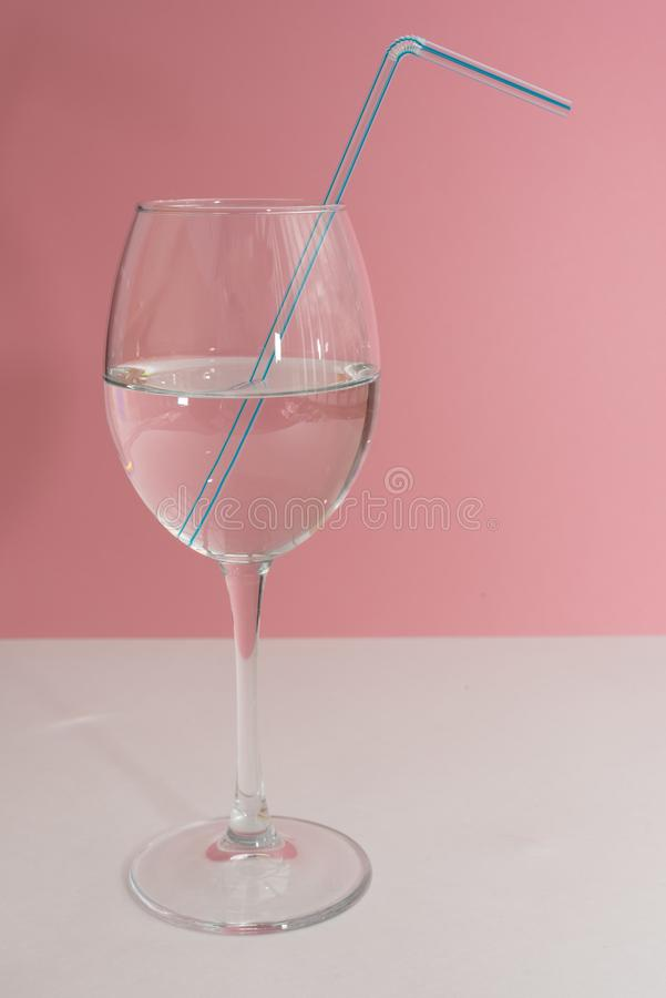 Blauer Trinkhalm im Weinglas voll mit Wasser auf wei?er Tabelle und rosa Hintergrundabschlu? oben Kopienraum, moc oben stockbild