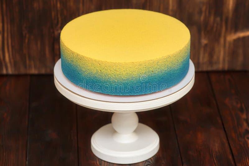 Blauer und gelber Kuchen auf Stand über hölzernem Hintergrund stockbilder