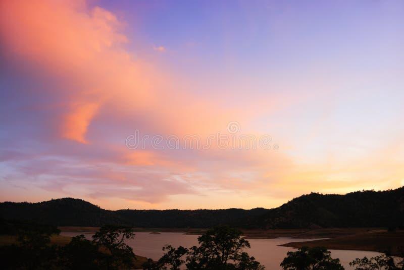 Blauer und orange Sonnenuntergang über See stockfotografie