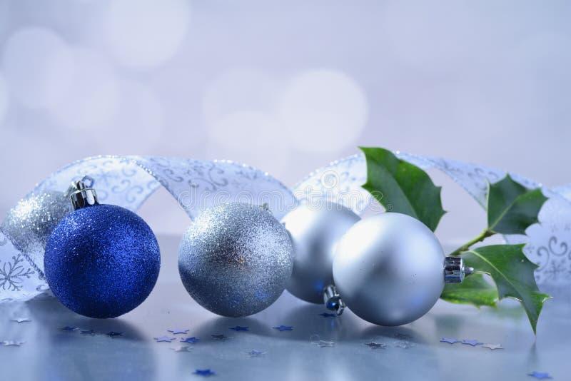 Blauer und weißer Funkeln Weihnachtsball mit dekorativem Band und Stechpalmenbaumast lizenzfreie stockfotos
