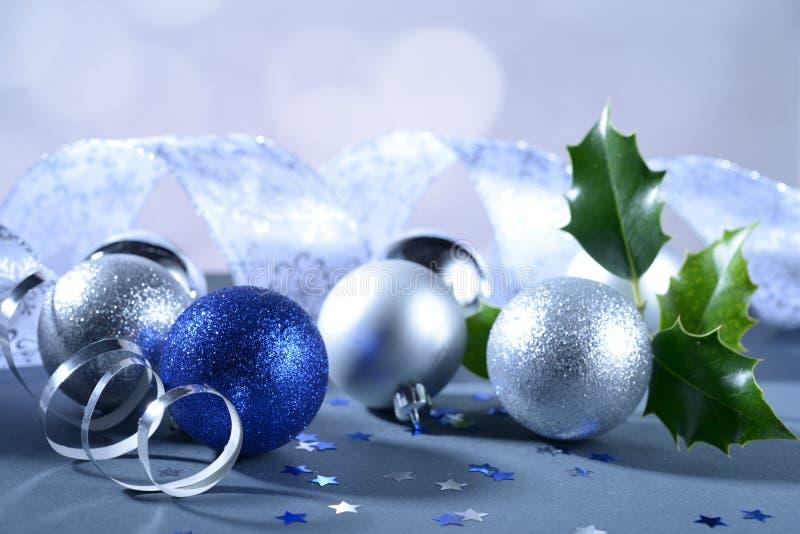 Blauer und weißer Funkeln Weihnachtsball mit dekorativem Band und Stechpalmenbaumast stockfotografie