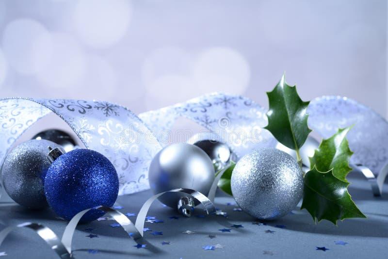 Blauer und weißer Funkeln Weihnachtsball mit dekorativem Band und Stechpalmenbaumast lizenzfreies stockfoto