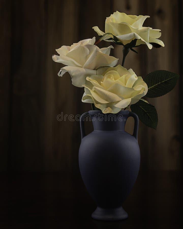 Blauer Vase mit gelben Rosen stockfotografie