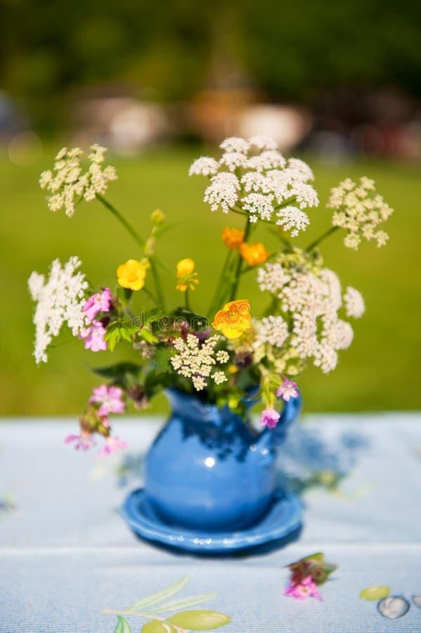 Blauer Vase mit wilden Blumen lizenzfreies stockbild