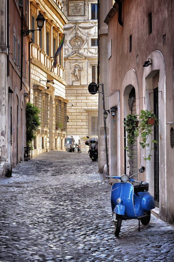 Blauer Vespa in der alten Straße von Rom lizenzfreie stockbilder