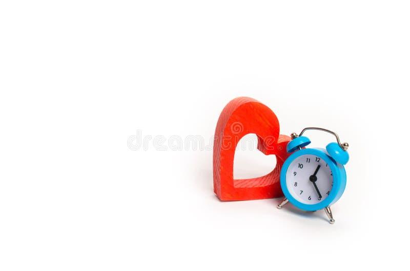 Blauer Wecker und rotes Herz auf einem weißen Hintergrund Das Konzept der Zeit und der Planung minimalismus Lebenserwartung Vertr lizenzfreies stockfoto