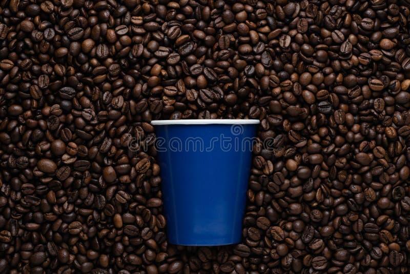 Blauer Wegwerftasse kaffee, zum auf den Hintergrund von gebratenen Bohnen zu gehen stockfotografie