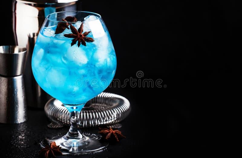 Blaues alkoholisches Cocktail mit sambuca, Likör, Zitronensaft, zerquetschtem Eis und Anissternen im großen Weinglas mit Barmixer stockfotografie