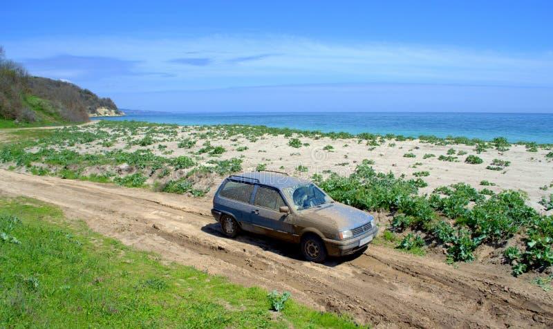 Blaues Auto bedeckt im Schlamm auf Schotterweg zu einem Strand lizenzfreie stockfotos