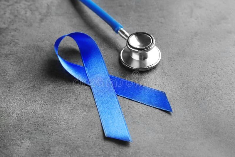 Blaues Band und Stethoskop auf grauem Hintergrund lizenzfreie stockfotografie