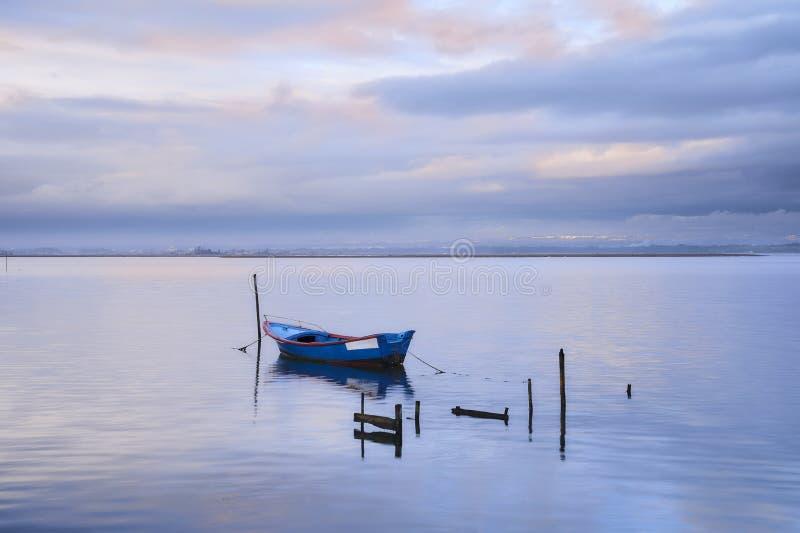 Blaues Boot mitten in dem See unter Rosa und blauem Himmel lizenzfreies stockfoto